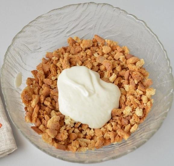 Столовую ложку крема смешиваем с половиною крошек, что получились от наших коржей.