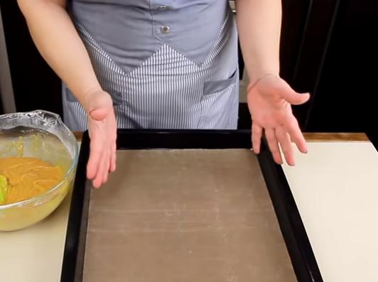 Застилаем противень пергаментной бумагой и выкладываем на него половину замешенного теста. Духовку предварительно нагреваем до 180 градусов.