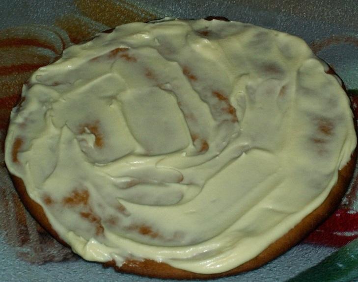 Формируем коржи в торт на ровной поверхности. Для этого подойдёт плоская тарелка. Укладываем на неё первый корж и смазываем кремом.